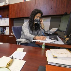 Staff in mask on phone for covid questions