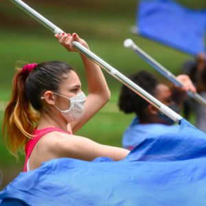 Students in masks practicing their flag routine for band